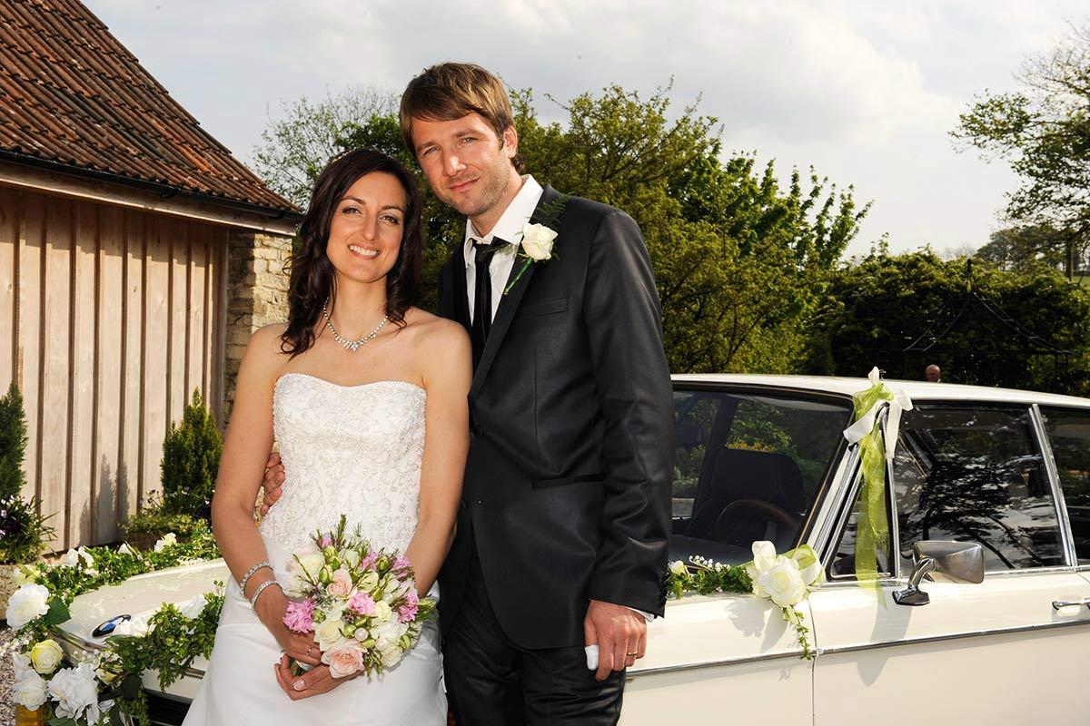 Honeylight Hochzeitsfotograf: Brautpaar vor BMW Hochzeitsauto