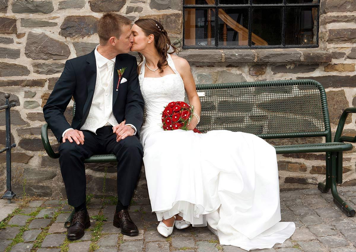 Hochzeitsfotograf Hagen: Brautpaar küsst sich auf einer Bank im Hagener Freilichtmuseum
