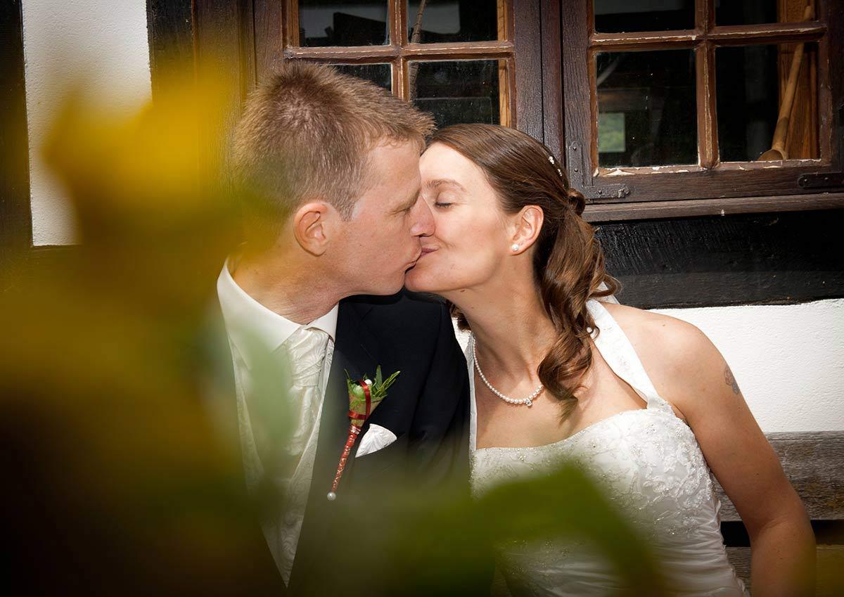 Hochzeitsfotograf Hagen: Junges Brautpaar küsst sich auf einer Bank vor Fachwerkhaus im Hagener Freilichtmuseum