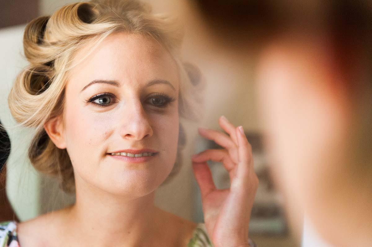 Honeylight Hochzeitsfotografen: Braut in Hochzeitsvorbereitung schaut in den Spiegel