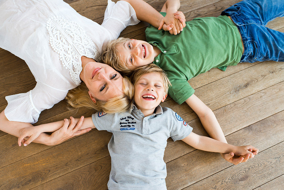 Familienfotografie Honeylight: Mutter mit 2 Kindern auf dem Holzboden