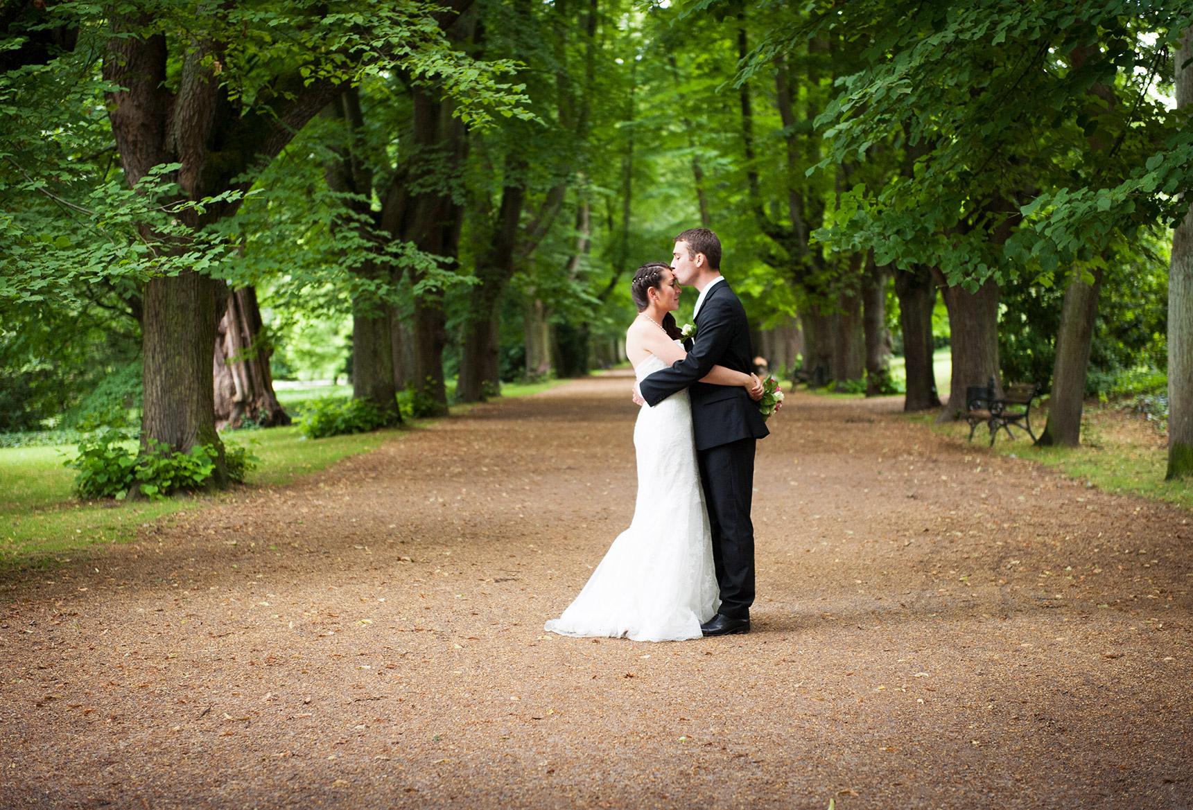 Hochzeitsfotografie Honeylight: Hochzeitsfotos vom Brautpaar das sich im Dortmunder Rombergpark küsst