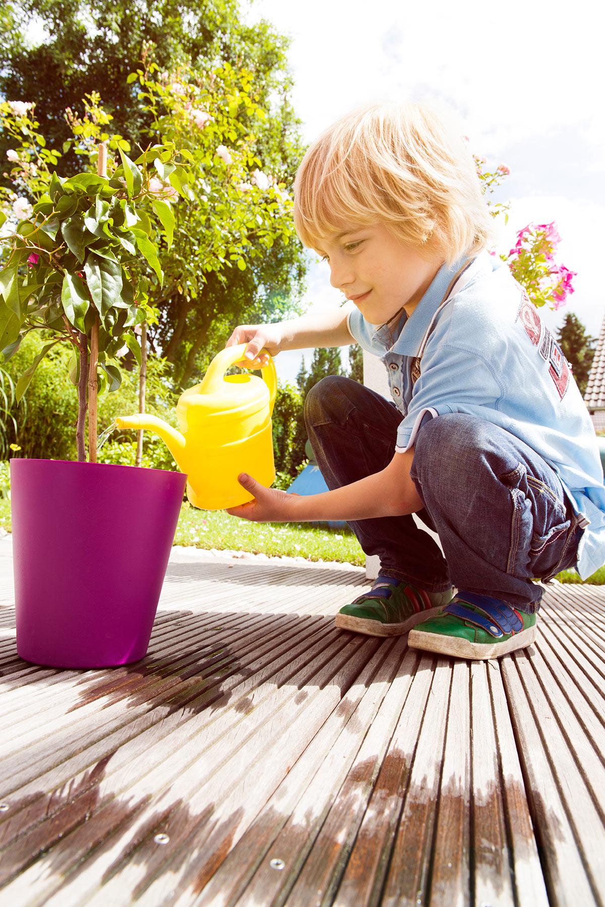 Familienfotografie Honeylight : Ein junges Kind gießt im Garten Blumen.