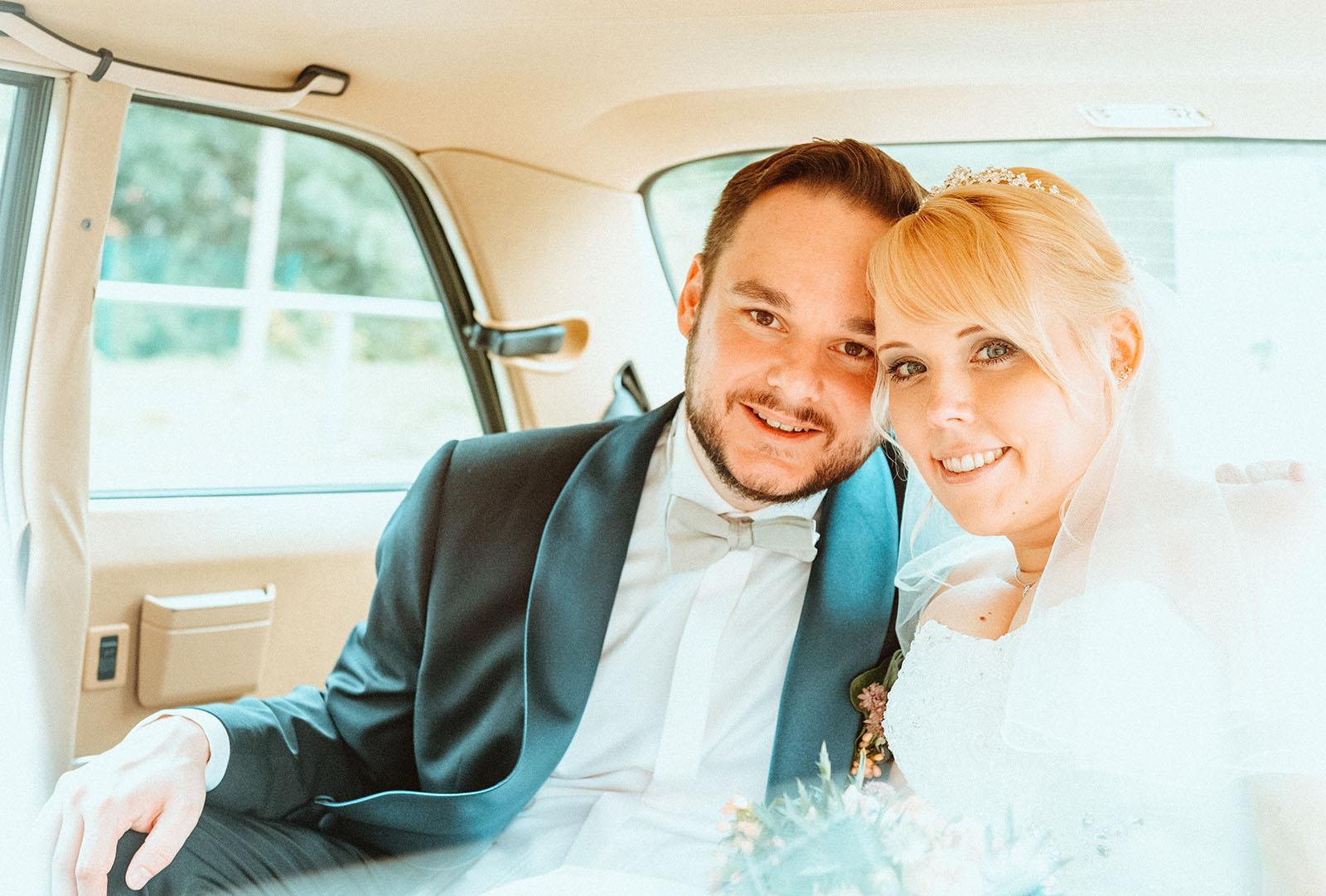 Brautpaar im Hochzeitsauto