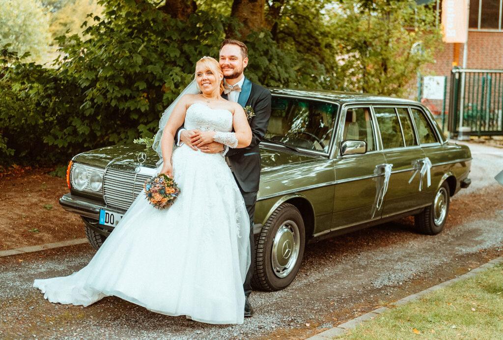 Hochzeitsshooting mit Brautpaar vor Hochzeitsauto