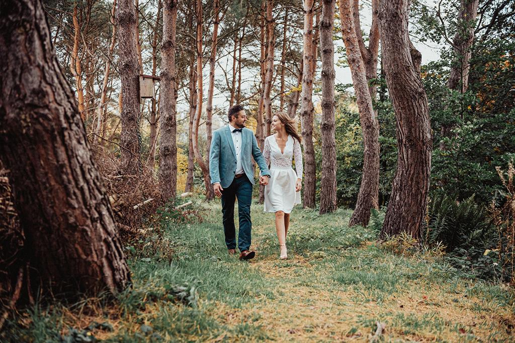 Brautpaar geht durch Baumallee im Rombergpark